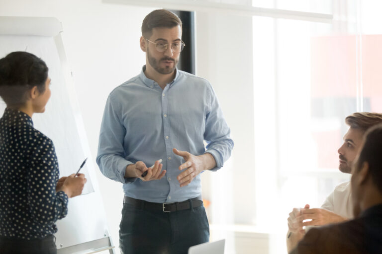 Male coach manager speak at corporate workshop give flip chart presentation for employees clients group, serious speaker presenter consult training explain business strategy at team meeting concept